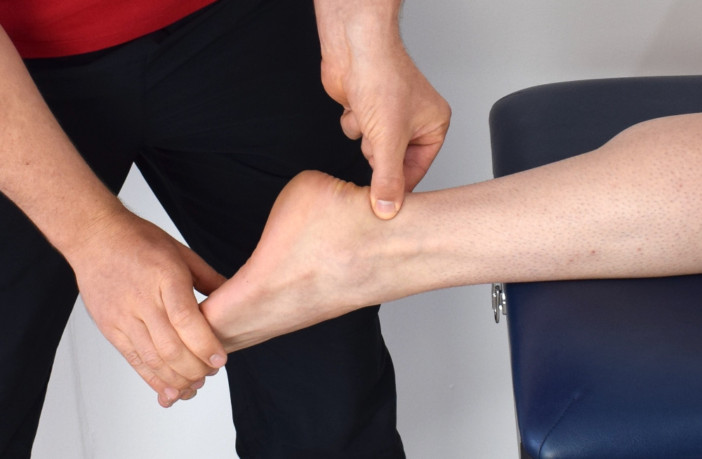 Physical therapist stretches patient's ankle