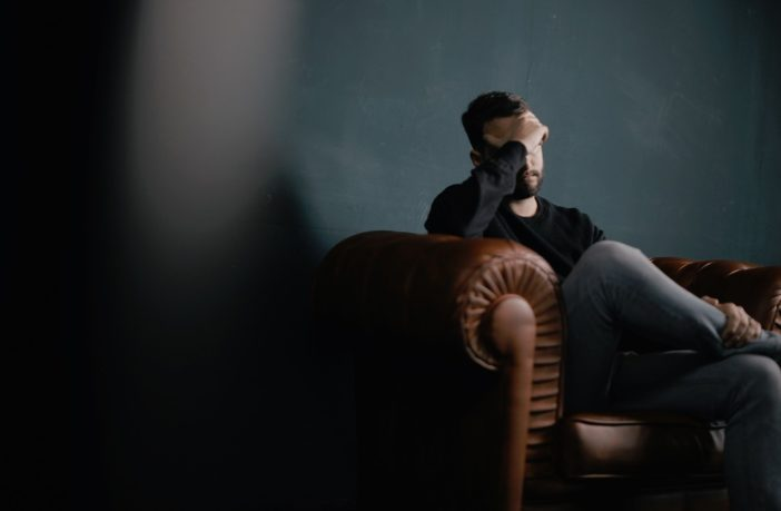 Man sitting in leather chair with headache