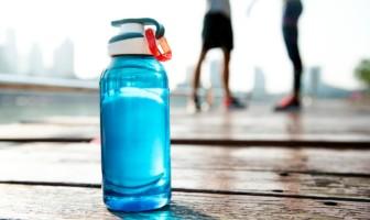 Blue reusable water bottle on a wooden boardwalk