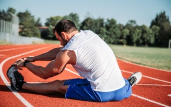 Man stretching his legs on a track