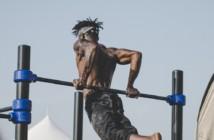 man doing gymnastics on pull up bar