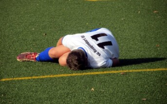 Soccer player laying on turf grabbing knee
