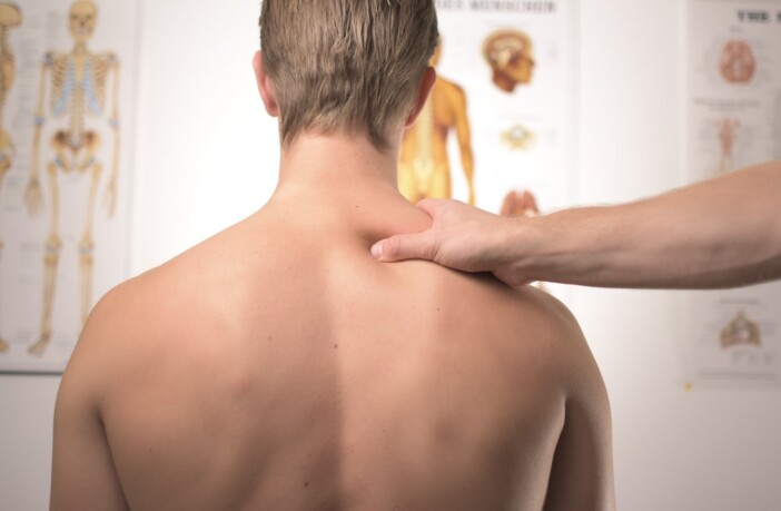 Man receiving neck and shoulder treatment at physical therapist