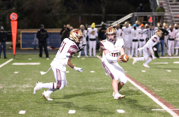 Brett Griffis of Broad Run Football hands the ball off to Kyle Davis during the Spartans' win at Loudoun County on February 23 in Leesburg