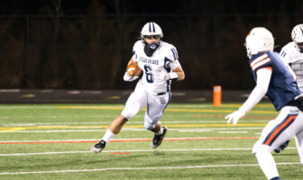 Stone Bridge junior running back Eli Mason carries the ball in a win over Briar Woods on March 5 in Ashburn